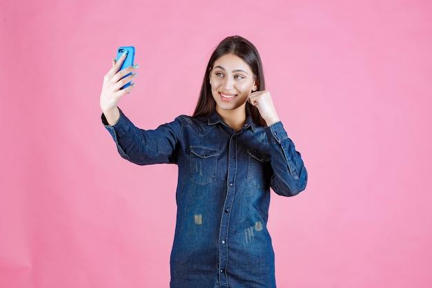 Dziewczyna nawiązywania połączenia wideo lub robienia selfie