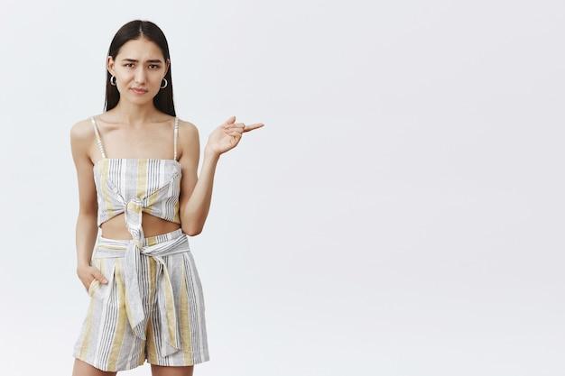Dziewczyna nie jest pewna, czy nowy model pasuje do składu. portret niepewnej i wątpliwej niezadowolonej kobiety w modnym stroju, wskazującej w prawo i mrużącej oczy z wahaniem, niepewnej na szarej ścianie