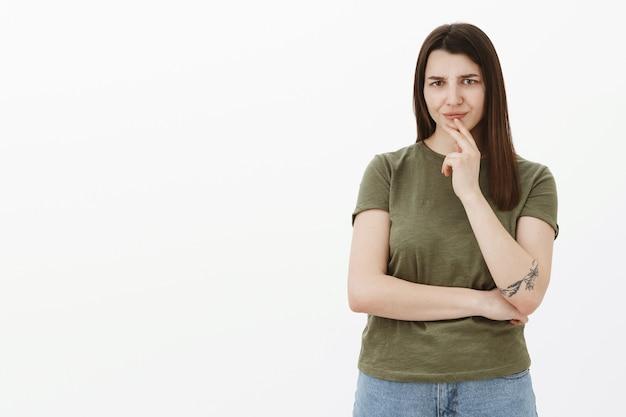 Dziewczyna nie lubi tego, co słyszy, marszczy brwi z powodu niechęci i zmieszania trzymając dłoń nad ustami, mrużąc oczy i krzyżując jedną rękę na ciele, słysząc bzdury i rozczarowującą sugestię