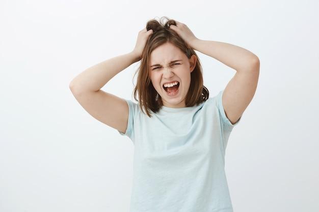 Dziewczyna nienawidzi za dużo myśleć. niezadowolona, zdenerwowana młoda zdenerwowana europejka z brązową krótką fryzurą krzycząca, tracąca panowanie nad sobą, wściekła lub szalona, psująca lub wyrywająca włosy z głowy