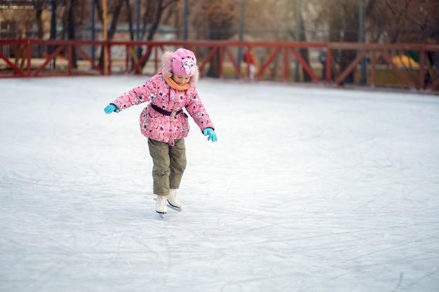 Dziewczyna niepewnie stoi na łyżwach figurowych na lodowisku i próbuje jeździć