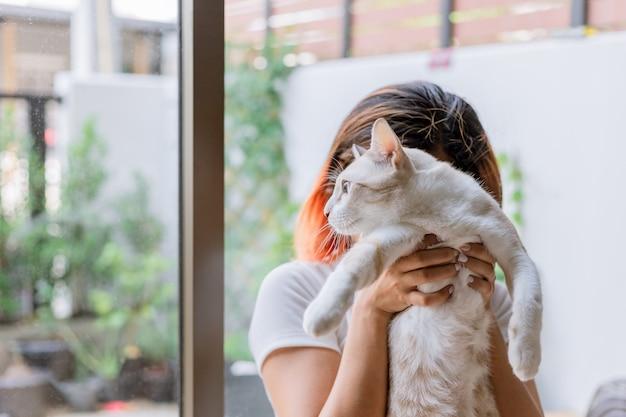 Dziewczyna niesie jej kot przyszedł, by ukryć twarz.