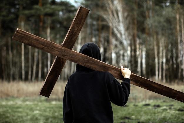 Dziewczyna niesie krzyż. nieście krzyż. człowiek wierzy w boga. nadzieja w bogu.