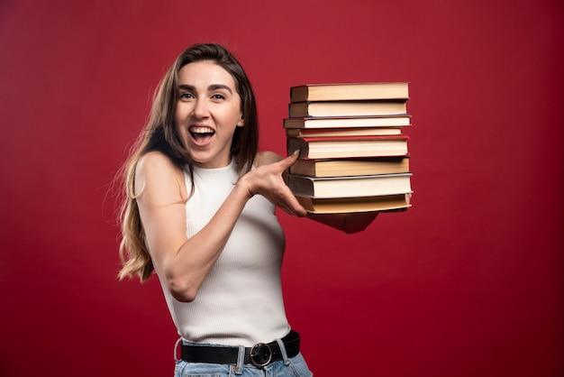 Dziewczyna niesie stos książek