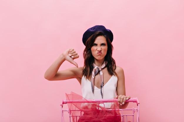 Dziewczyna niezadowolona z zakupów i pokazuje kciuk w dół. zdenerwowana kobieta w białej bluzce iz szalikiem na szyi, pozowanie na różowym tle.