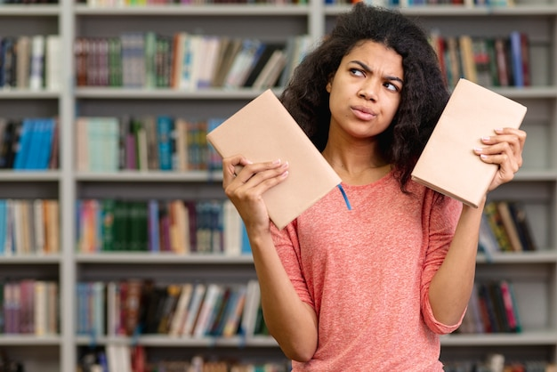 Dziewczyna niezdecydowana wybrać książkę do przeczytania