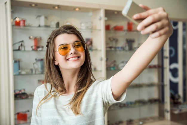 Dziewczyna nigdy nie mieszka w domu bez smartfona, stylowa europejska brunetka przymierza okulary przeciwsłoneczne podczas robienia selfie na telefonie, uśmiecha się szeroko
