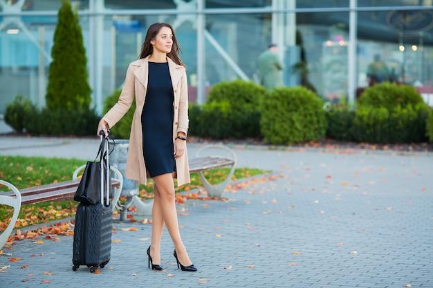 Dziewczyna niosąca walizkę ulicami. uśmiechnięty blond bizneswoman z kołowym bagażem