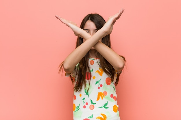 Dziewczyna nosi letnie ubrania na czerwonej ścianie utrzymującej skrzyżowane ręce, odmowa.