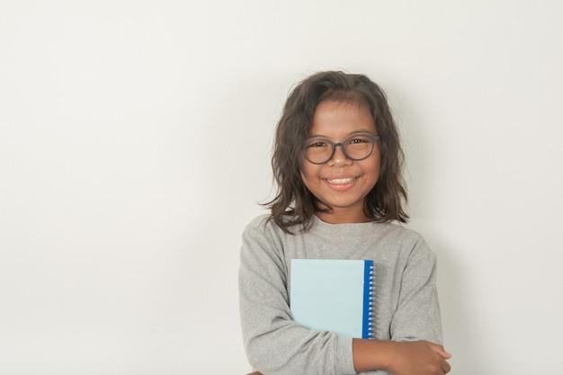 Dziewczyna nosi okulary, robi zdjęcie twarzy i patrzy w kamerę. w objęciach jest książka jasna i urocza. szara scena