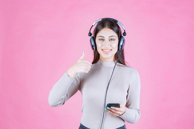 Dziewczyna nosi słuchawki i słucha muzyki