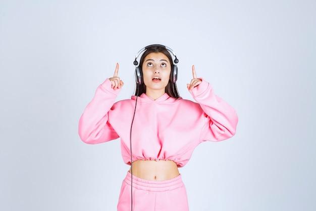 Dziewczyna nosi słuchawki i wskazuje do góry nogami. wysokiej jakości zdjęcie