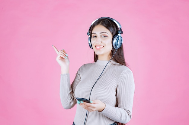 Dziewczyna nosi słuchawki i wskazuje gdzieś