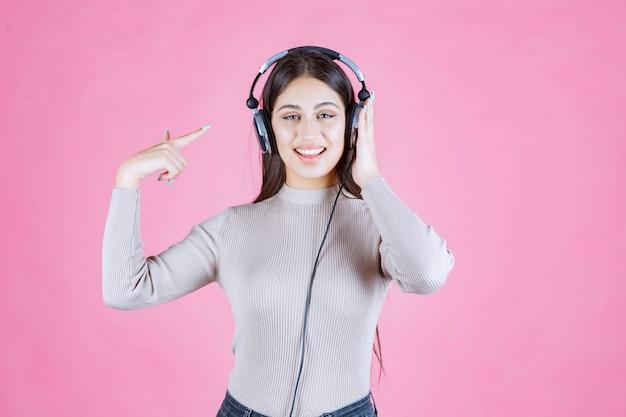 Dziewczyna nosi słuchawki i wskazuje na nich
