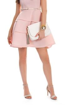 Dziewczyna nosi sukienkę z łososia. mały zegarek na rękę i torebka. piękna odzież z dodatkami. suknia wieczorowa z małym paskiem.
