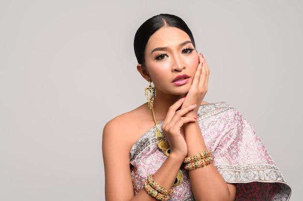 Dziewczyna nosi tajską sukienkę, a dłonie dotykają twarzy.