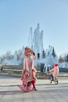 Dziewczyna nowa moda vogue kreatywne ubrania pozowanie na zewnątrz, różowa sukienka i kapelusz, etniczne ubrania
