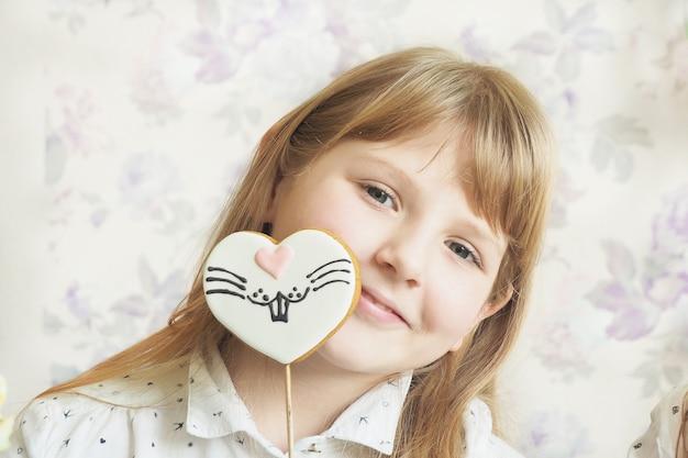 Dziewczyna o blond włosach z luźnymi włosami od 10 lat trzyma w dłoniach piernik na kształcie serca w kształcie serca i wychodzi zza pomalowanej twarzy zająca.