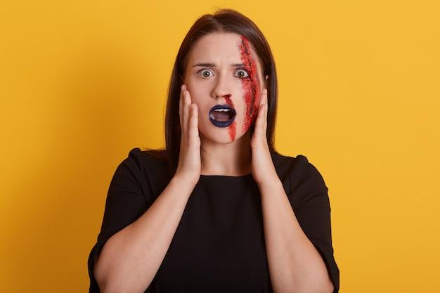 Dziewczyna o ciemnych, prostych włosach, z zakrwawioną raną na twarzy, dużymi oczami pełnymi strachu, lekko zmrużona, widzi przed sobą wampira, mordercę lub psychika, halloweenową koncepcję.