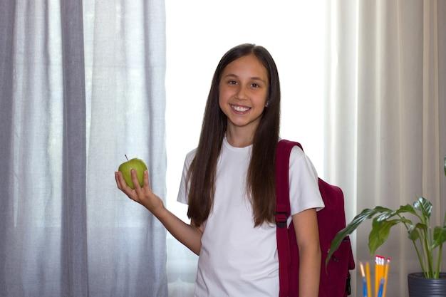Dziewczyna o ciemnych włosach stoi przy stole w domu z jabłkiem szkolny plecak przed pójściem do szkoły
