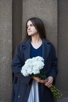 Dziewczyna o ciemnych włosach trzyma w rękach bukiet niebieskich goździków na szarej ścianie