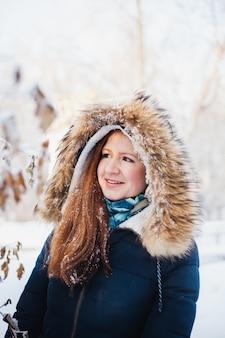 Dziewczyna o europejskim wyglądzie na spacerze w zimowym lesie, parku, zimie i śniegu, zdrowiu, zimowych ubraniach, kurtce