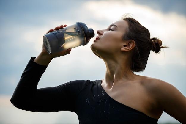 Dziewczyna o europejskim wyglądzie ze sportową budową w czarnym topie i czarnych legginsach na tle błękitnego nieba. pije wodę z butelki. zdrowy styl życia, sportowa brunetka dziewczyna. motywacja do sportu