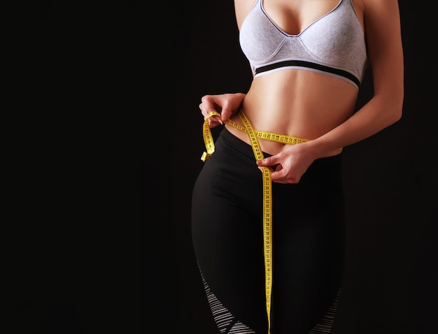 Dziewczyna o idealnej figurze sportowej mierzy wielkość talii