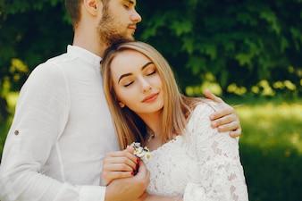 Dziewczyna o jasnych włosach i białej sukience w słonecznym lesie ze swoim chłopakiem
