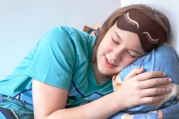 Dziewczyna o jasnych włosach leży z zamkniętymi oczami na poduszce i obejmuje ją ramieniem.