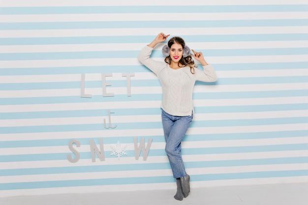 Dziewczyna o ładnym wyglądzie i dobrym poczuciu humoru pozuje do zdjęcia na tle pięknej ściany. portret ciemnowłosej damy z różową szminką