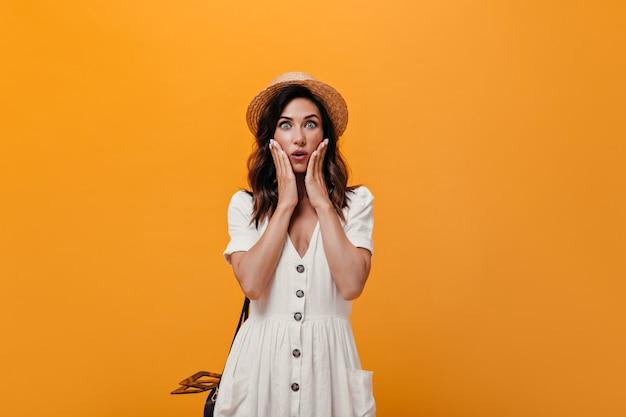 Dziewczyna o niebieskich oczach wpatruje się ze zdziwienia w kamerę na pomarańczowym tle. ładna kobieta o ciemnych włosach w słomkowym kapeluszu i białej sukni cuda.