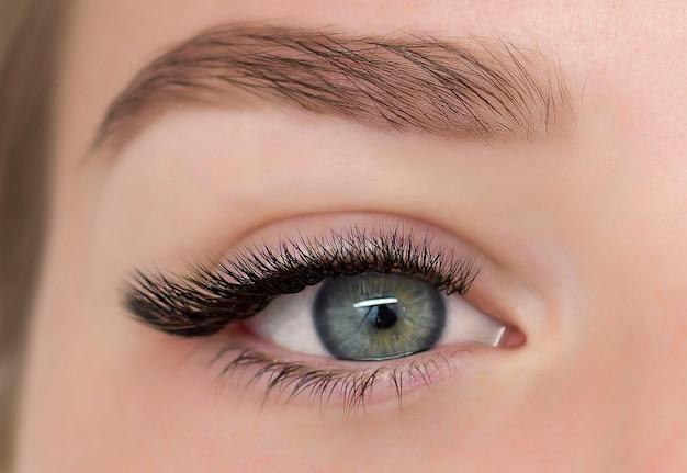 Dziewczyna o pięknych zielonych oczach pomalowanych czarnymi rzęsami. zbliżenie oczu.
