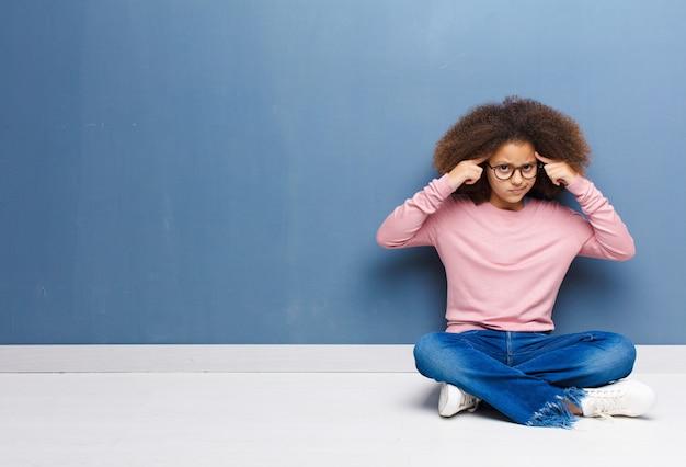 Dziewczyna o poważnym i skoncentrowanym spojrzeniu, burzy mózgów i myśli o trudnym problemie