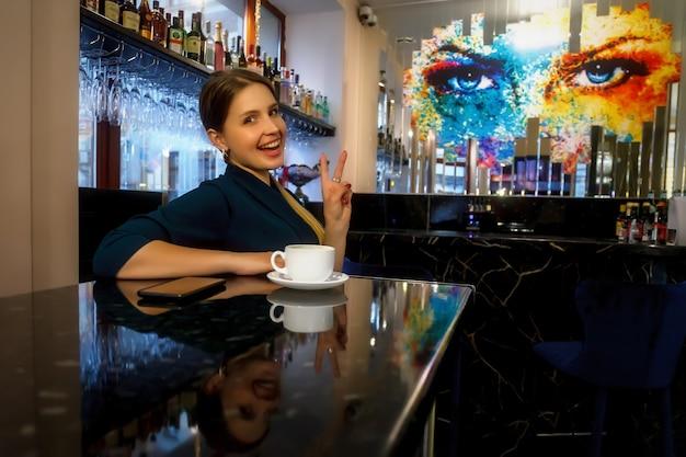 Dziewczyna o słowiańskim wyglądzie w barze, kawiarni lub restauracji z białym kubkiem. kobieta pokazuje emocje. młoda urocza kobieta siedzi przy barze i pije kawę lub herbatę w wolnym wieczornym czasie
