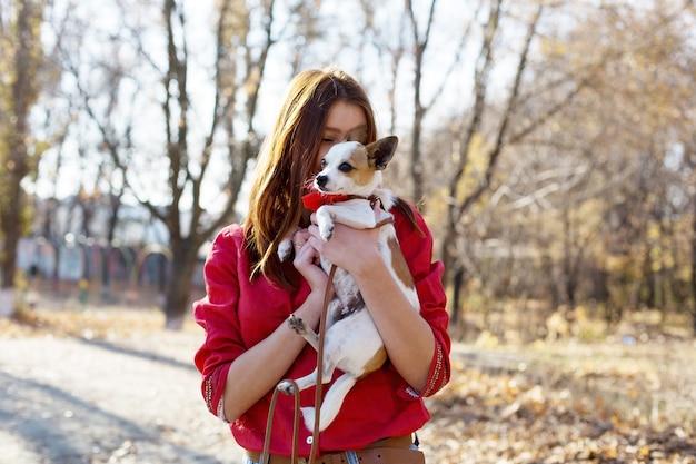 Dziewczyna obejmuje szczeniaka, zabawkowy pies terier ze smyczą na zewnątrz, zwierzęca miłość