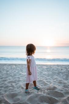 Dziewczyna od tyłu i biała sukienka stojąca na letniej plaży patrząc na zachód słońca