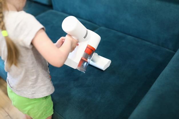 Dziewczyna odkurzająca sofa z bezprzewodowym odkurzaczem