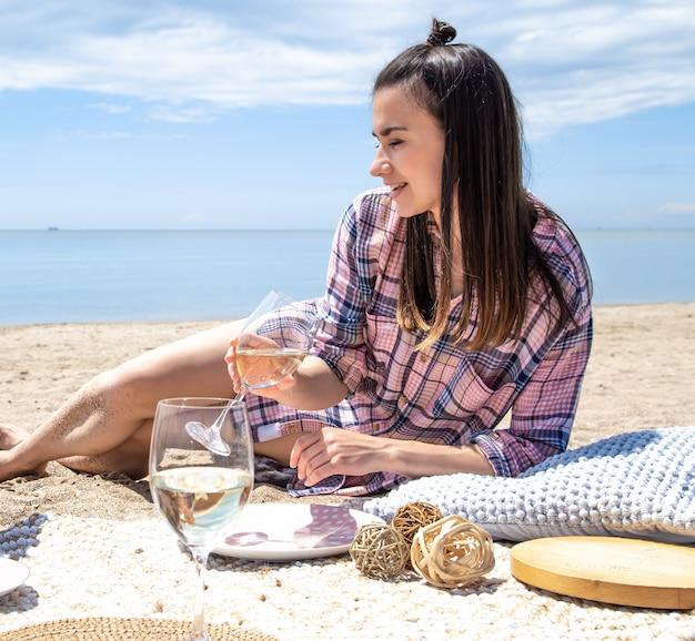 Dziewczyna odpoczywa na plaży. romantyczny piknik na piaszczystej plaży. pojęcie wakacji.
