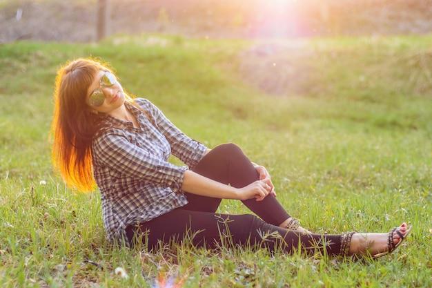 Dziewczyna odpoczywa na polu o zachodzie słońca w lecie