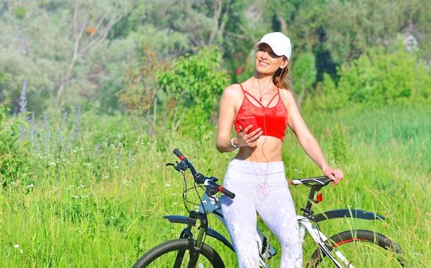 Dziewczyna odpoczywa na rowerze po jeździe na rowerze na świeżym powietrzu i słuchaniu muzyki ze smartfona