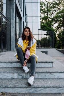 Dziewczyna odpoczywa na schodach. atrakcyjne modne modne modne hipster dziewczyny spaceru ulicami miasta.