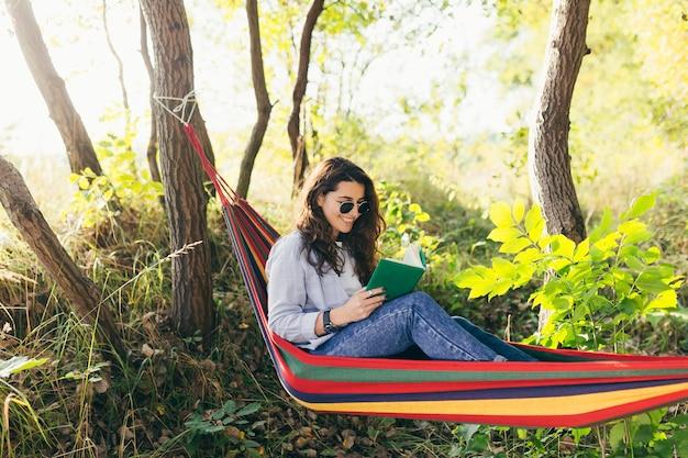 Dziewczyna odpoczywa w parku z książką na hamaku