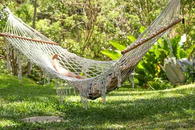 Dziewczyna odpoczywa w przytulnym hamaku w tropikalnym ogrodzie na wyspie bali, indonezja, miejsce odpoczynku i relaksu