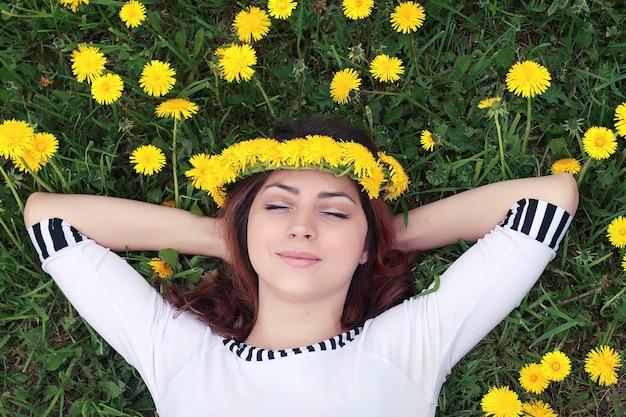 Dziewczyna odpoczywa w słoneczny dzień na łące żółtych mleczy