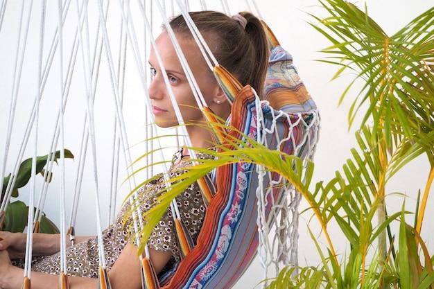 Dziewczyna odpoczywa wieczorem na balkonie, siedząc na wiszącym krześle. czas letni