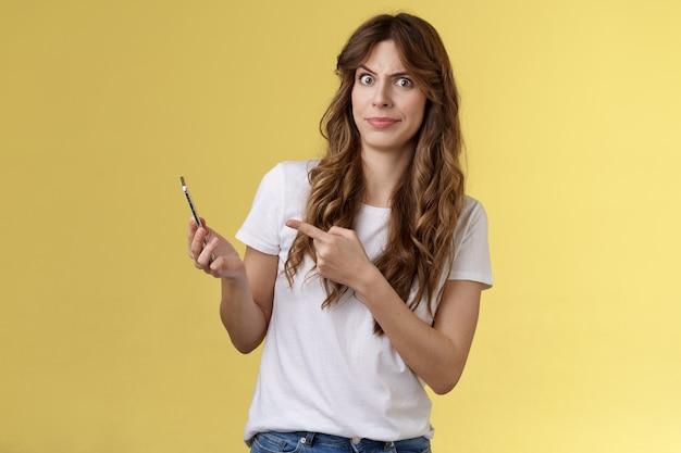 Dziewczyna odpowiada dziwny dziwny telefon odbierać szaloną denerwującą wiadomość krzywić się wątpliwe niezadowolone uśmiechać się przerażenie wskazując podejrzany stojak na smartfona żółte tło intensywny sfrustrowany