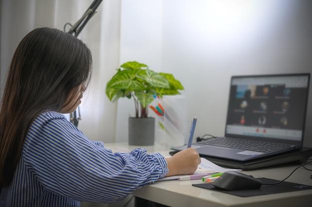 Dziewczyna odrabiająca pracę domową lub edukację online
