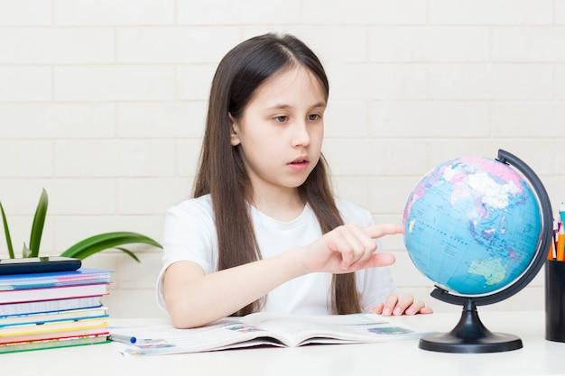 Dziewczyna odrabiająca pracę domową, patrząc na światową koncepcję edukacji na odległość online z powrotem do szkoły