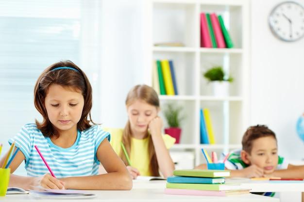 Dziewczyna odrabianiu lekcji siedzi przy biurku